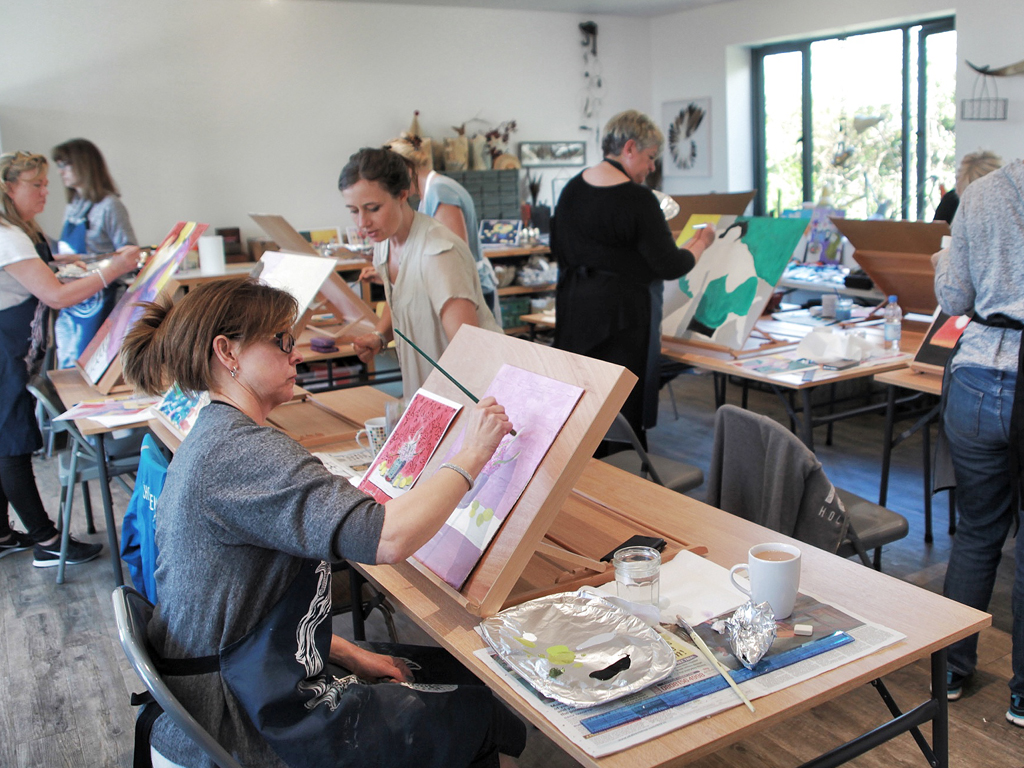 In the creative zoen, a group of ladies relax and enjoy being creative with colour